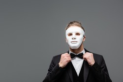 elegant businessman in face mask adjusting bow tie isolated on grey