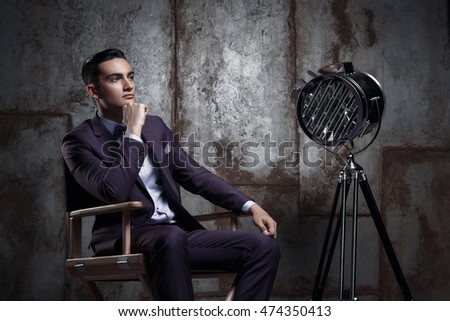 Elegant businessman in fashionable suit posing in the photo studio. luxury portrait of a man sitting in the director's chair next to the model is a retro movie spotlight