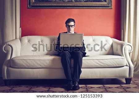 Elegant businessman on a white sofa with a laptop computer