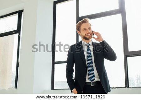 elegant businessman talking and having a nice conversation on cellphone happy and smiling on his office with big windows behind