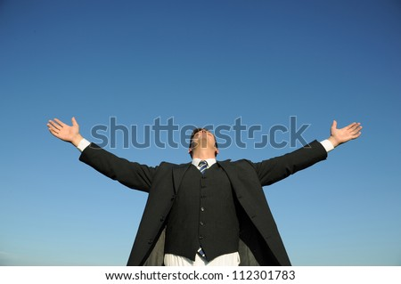 Elegant businessman with arms open, blue sky. Above space for text or graphics.