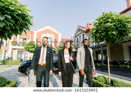 Elegant businesspeople, African and Caucasian man, Caucasian woman, walking outdoors on the yard of modern office business center.