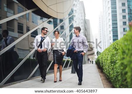 Elegant businesspeople walking in a modern city.