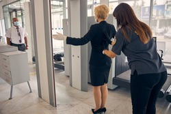 Elegant businesswoman in skirt suit passing through security check in airport terminal