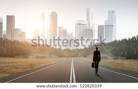 Elegant businesswoman on road standing with back and looking ahead Stock photo ©