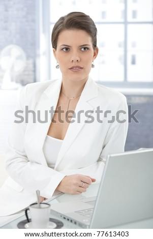 Elegant businesswoman sitting at desk, using laptop computer, thinking.?
