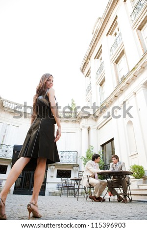 Elegant businesswoman walking to a meeting in a luxury building coffee shop terrace, outdoors.