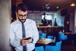Elegant caucasian bearded handsome businessman in shirt, tie and with eyeglasses leaning on wall in cafe and using smart phone for reading or sending message.