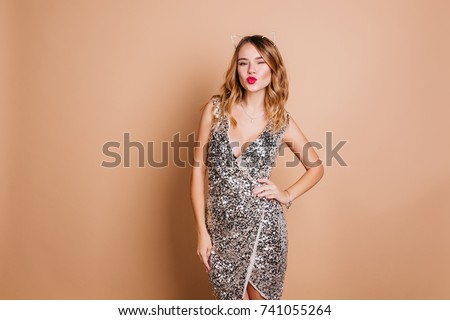 Elegant caucasian woman with curly hairstyle posing with kissing face expression at  party. Charming birthday girl in sparkle dress standing in confident pose on light background. #741055264