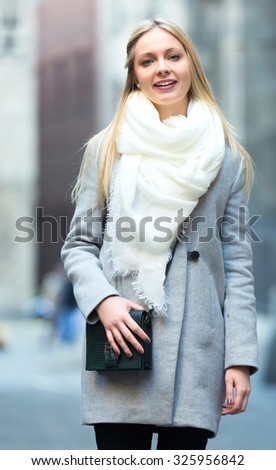Elegant charming young blonde walking on a city street outdoors dressed in a warm coat and scarf