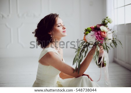 Elegant charming young brunette bride is sitting on white rustic wooden floor in a wedding dress with a big bouquet of flowers, daydreaming,  in the interior Waiting for groom. #548738044