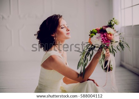 Elegant charming young brunette bride is sitting on white rustic wooden floor in a wedding dress with a big bouquet of flowers, daydreaming, in the interior Waiting for groom. #588004112