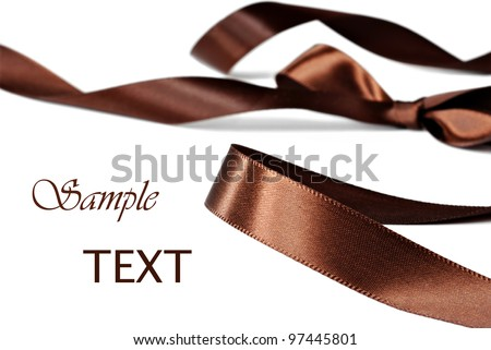 Elegant chocolate brown satin ribbon on white background with copy space.  Macro with extremely shallow dof.