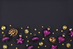 Elegant Christmas flat lay with purple tree ornament baubles, golden fir cones and bells on dark background with empty copy space