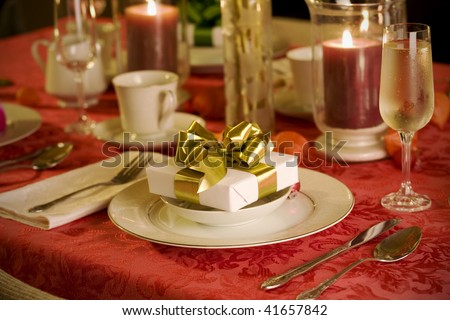 elegant Christmas table setting in red with gold gift as focal point - stock photo