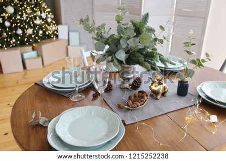 Elegant Christmas tree with gifts in the living room with dinner table near the textured gray walls in luxury apartments.