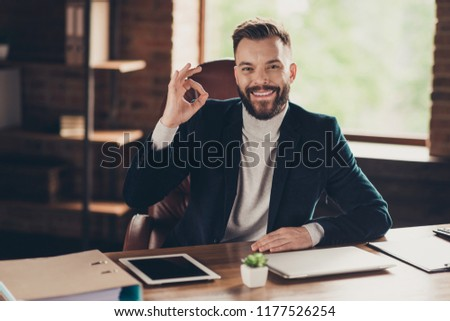 Elegant classic cheerful smart clever intelligent bearded content handsome attractive ceo, leader in black jacket, blazer, sitting at modern workplace, workstation, showing ok-sign