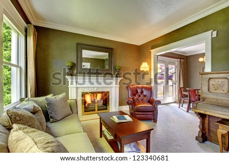Elegant classic green living room with fireplace and piano.