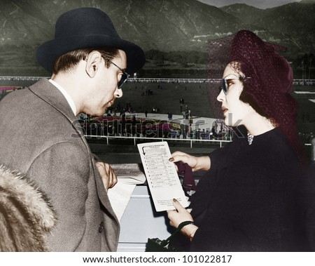 Elegant couple at a horse race looking at a program