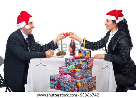 Elegant couple sitting at Christmas dinner table and husband giving his wife a present and both smiling and enjoy the time together