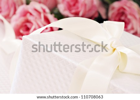 Elegant cream colored gift box with satin ribbon and bouquet of roses in background.  Macro with shallow dof and copy space.  Selective focus on corner of box and bow.