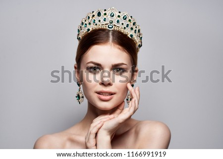 elegant crown elegant woman holds a hand near the face #1166991919