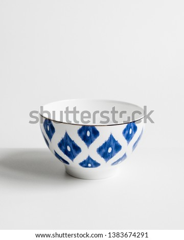 Elegant cutlery front view on a isolated white background. Porcelain soup bowl with blue rhombus and gold edging around the edge. Trendy plate pastel shades. Flat lay view.