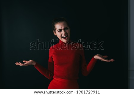 Elegant dark haired female in red outfit standing in confused pose with opened mouth and hands apart in studio on dark background Foto stock ©