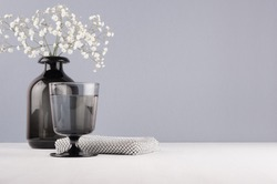 Elegant decor dressing table in minimalist style - black vase with flowers, glass, cosmetic accsssories silver bag on grey wall and white wood background.
