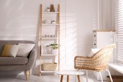 Elegant decorative ladder near sofa in living room