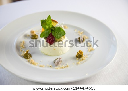Elegant dessert on a white dish with mint and red fruits and gold leaf