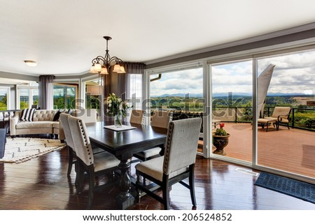 Photo of Elegant dining area with walkout deck in luxury house.