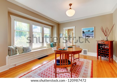 Elegant dining room with window bench with cherry hardwood floor and folk rug.