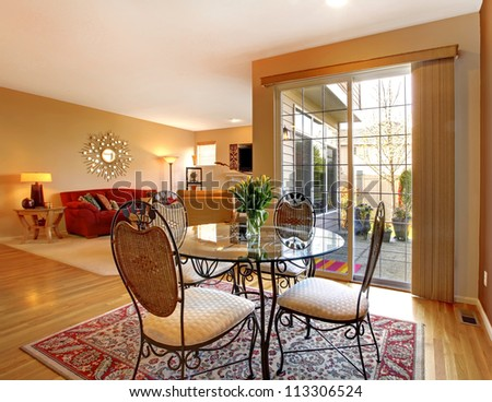 Elegant dining table near large door and living room.