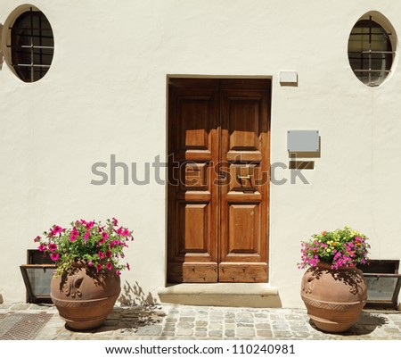 elegant doorway to the  house with terracotta containers for blooming plants,  Emilia - Romagna,Italy, Europe