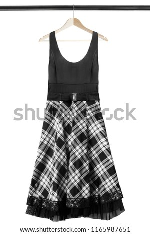 c9bb6594d37 Elegant dress with black and white tartan skirt hanging on wooden clothes  rack isolated over white