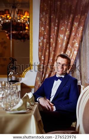 Elegant dressed cheerful businessman in glasses is sitting in luxury restaurant waiting for dinner in good mood.