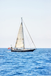 Elegant dutch cruising yacht sailing in a still water of an open Mediterranean sea on a clear day. Idyllic seascape. Summer vacations, leisure activity, sport and recreation, private wessel