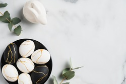 Elegant Easter flatlay composition. Luxury Easter eggs decorated with gold, rabbit bunny, eucalyptus leaves on marble table. Flat lay, top view