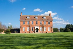 Elegant English Country Manor mansion house Grade 2 listed Victorian period property in red brick. Front view with large garden and green lawn