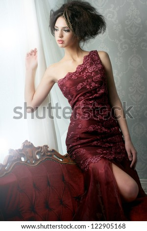 Elegant fashion bride in red wedding dress, looking out of the window.