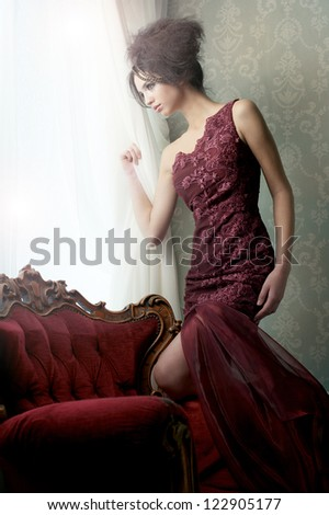 Elegant fashion model in red couture wedding dress looking out of the window in expectation.
