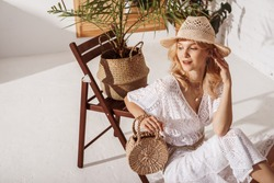 Elegant fashionable happy smiling woman wearing summer white crochet jumpsuit, many chains, straw hat, holding wicker bag, posing in stylish boho interior. Copy, empty space for text