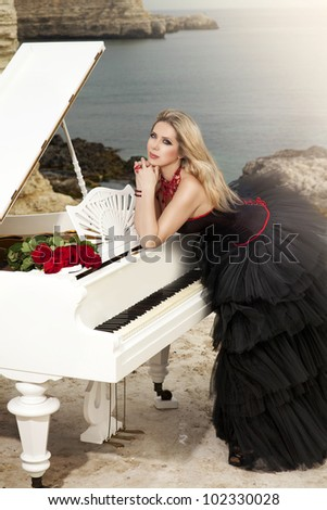 elegant fashionable woman in black dress with grand piano near sea shore at sunset. rich vintage lady musician with red roses - gothic bride spring summer