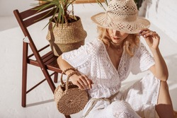 Elegant fashionable woman wearing summer white crochet jumpsuit, hiding her face with straw hat, holding wicker bag, posing in stylish boho interior. Copy, empty space for text