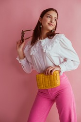 Elegant fashionable woman wearing white vintage blouse with lace collar, pink jeans, holding small padded yellow leather bag, posing on pink background