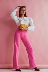 Elegant fashionable woman wearing white vintage blouse with lace collar, pink jeans, holding small padded yellow leather bag, posing on pink background. Full length portrait