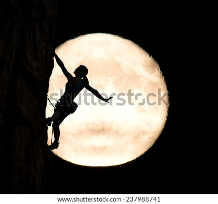 Elegant female extreme climber and big moon. Silhouette of female rock climber hanging on her hand on the vertical rock with big moon on the background