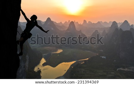Elegant female extreme climber silhouette against the sunset over the river. China, typical Chinese landscape with mountains and river