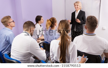 Elegant female teacher lecturing to students at the auditorium  #1558790513